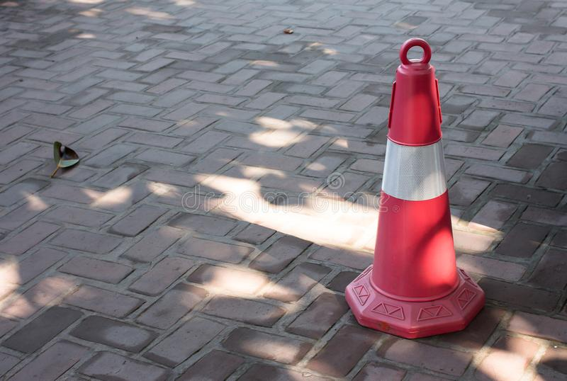 Traffic cone, with white and orange stripes on walkway. royalty free stock photos