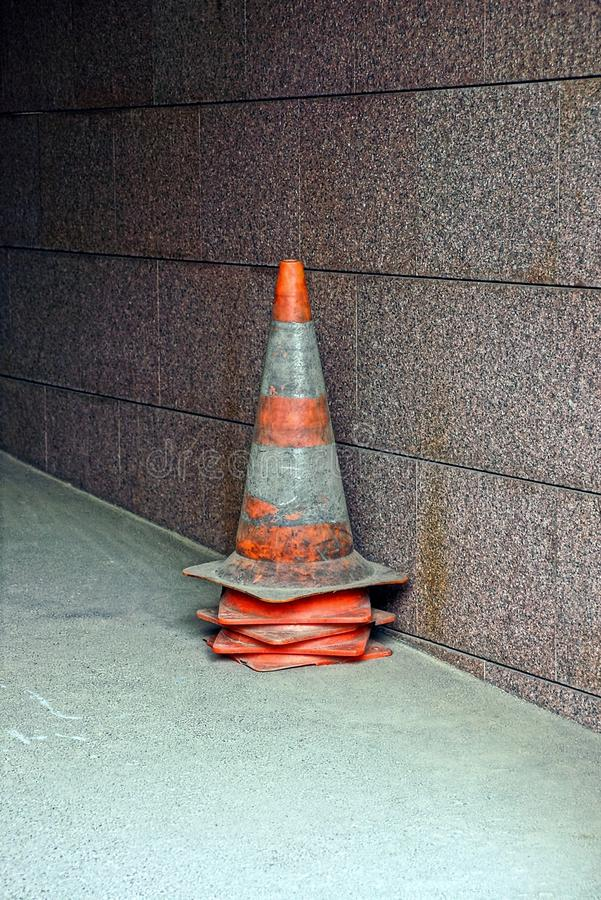 Traffic cones limiter in a pile near a wall. Road equipment for fencing near the wall stock photo