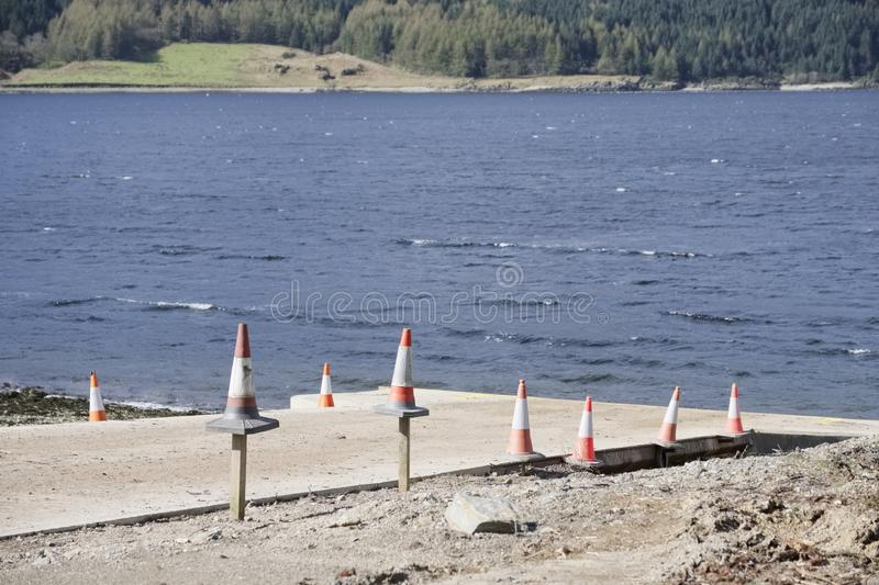 Traffic cones at slipway into sea loch on coast at boat ship launch for safety of fisherman. Uk stock photography