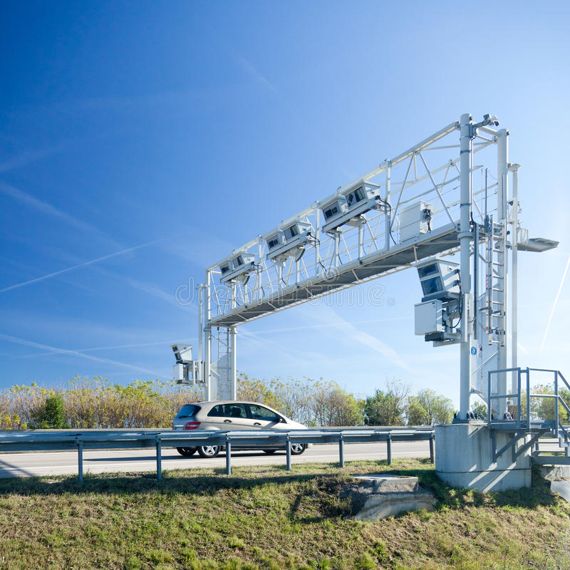 Traffic control sign over road. Modern traffic control signs on bridge over road with car passing underneath; blue sky background stock photo