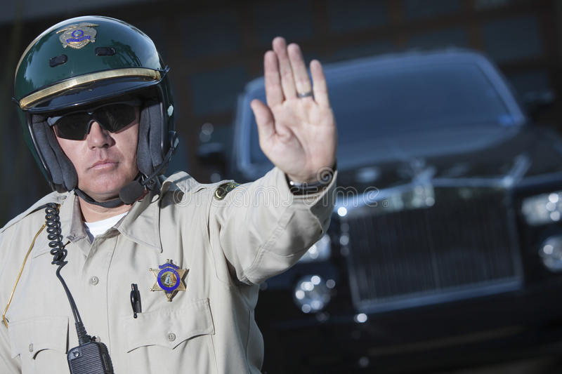 Download Traffic Cop Signaling Stop Gesture With Car In Background Stock Photo - Image: 33902298