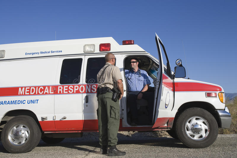 Traffic Cop Talking With EMT Doctor. Full length of a traffic cop talking with EMT doctor in ambulance royalty free stock photos