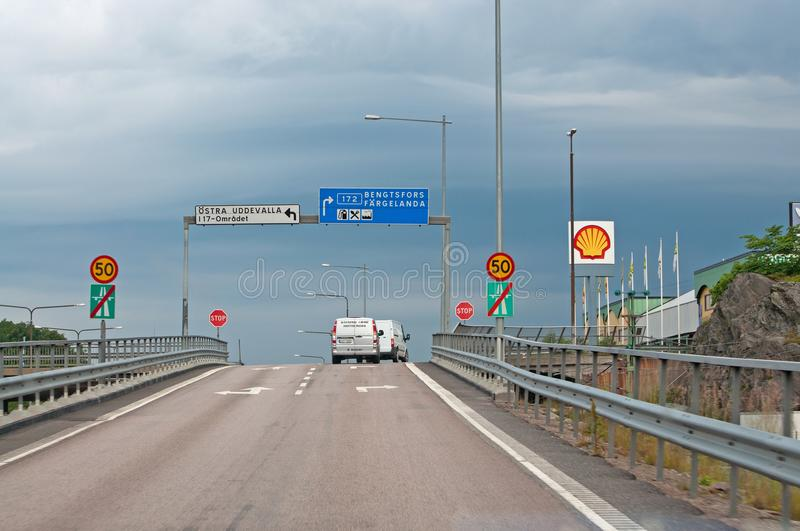 Traffic crossing off motorway with roadsigns. VANERSBORG, SWEDEN - JULY 1, 2012: Traffic crossing off motorway with roadsigns and speed limit signs on a summer stock photos