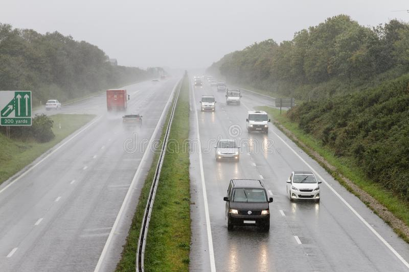 Traffic driving in heavy rain on dual carriageway. Traffic driving in heavy rain on a dual carriageway with headlights on in hazardous conditions royalty free stock photos