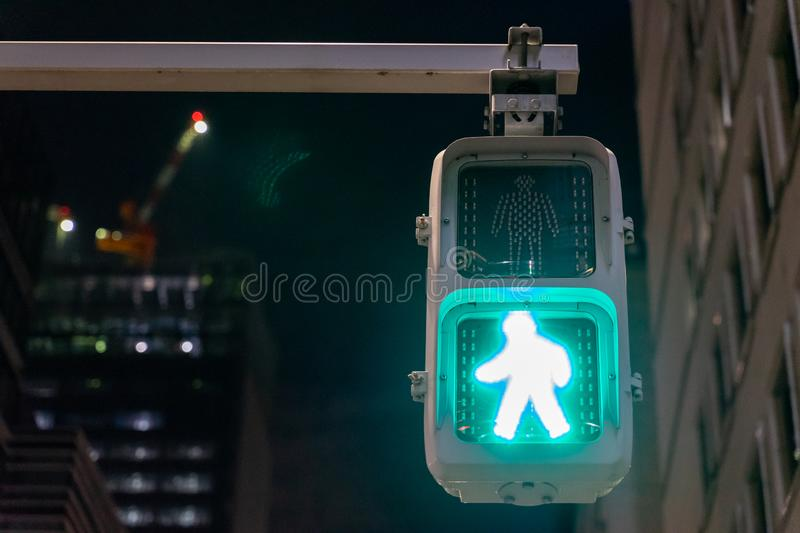 Traffic green light for people, pedestrian and human to cross the street in dark city night Tokyo, japan with background of office stock images