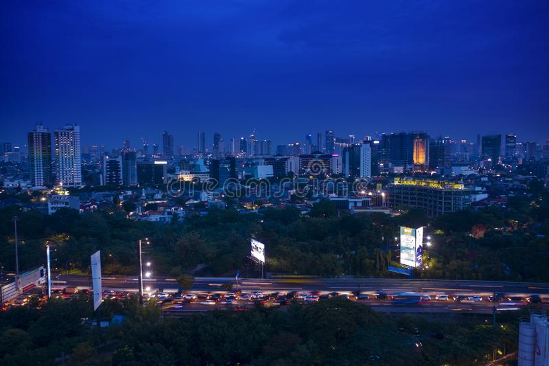 Traffic jam with Jakarta cityscape background at night. JAKARTA - Indonesia. March 20, 2019: Aerial view of traffic jam on the road with Jakarta cityscape royalty free stock photography