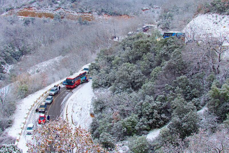 Traffic jam on narrow mountain road during snowstorm. Scenic winter nature landscape. Meteora, Greece-December 30, 2019: Traffic jam on narrow mountain road royalty free stock images