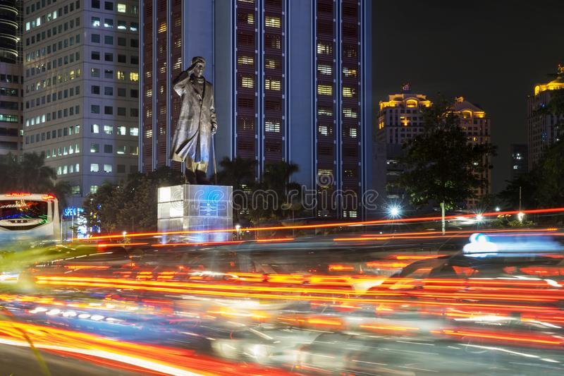 Traffic jam with Sudirman statue background. JAKARTA - Indonesia. March 29, 2019: Traffic jam with trail lights and Sudirman statue background at night time in royalty free stock image