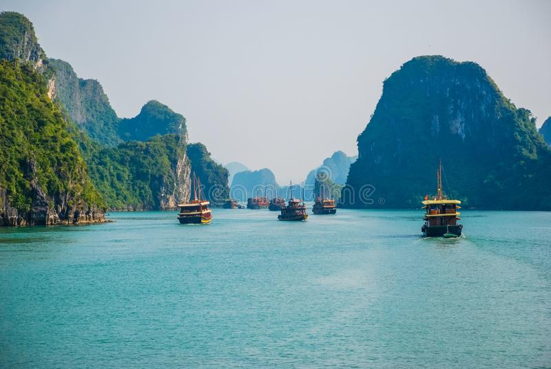 Traffic jam of traditional boats in Ha Long Bay. Traffic jam of traditional junks sailing through the islands of Ha Long Bay in Vietnam royalty free stock image