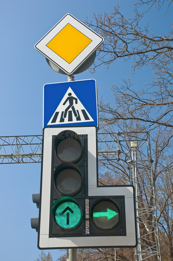 Traffic light. S and road signs against sky stock image