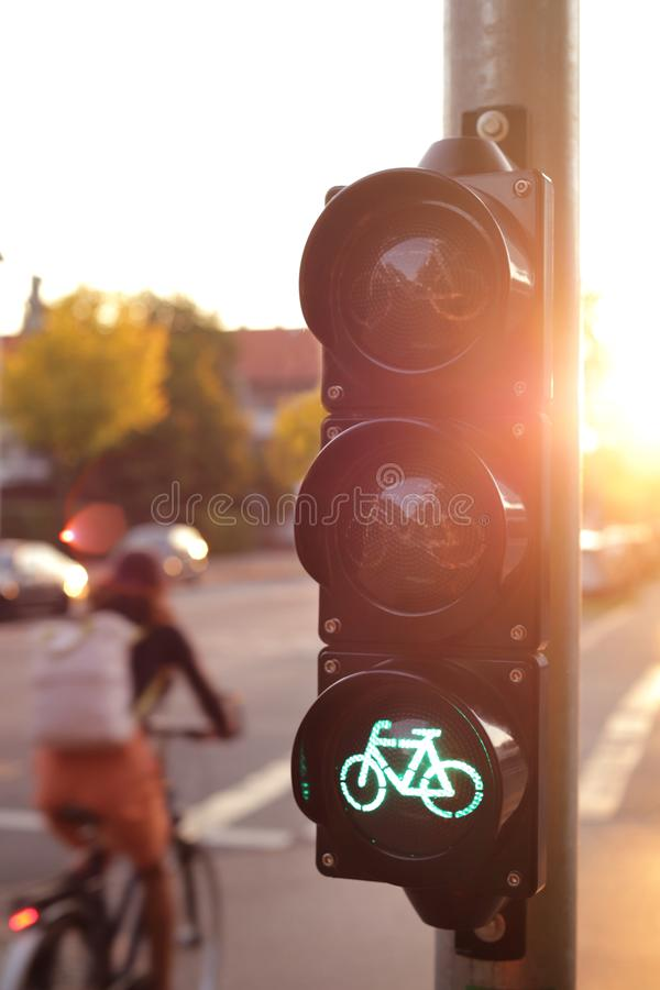Traffic light for a cycling lane showing green bicycle symbol in bright morning light with cyclist driving by in background. Traffic light for a cycling lane stock photo