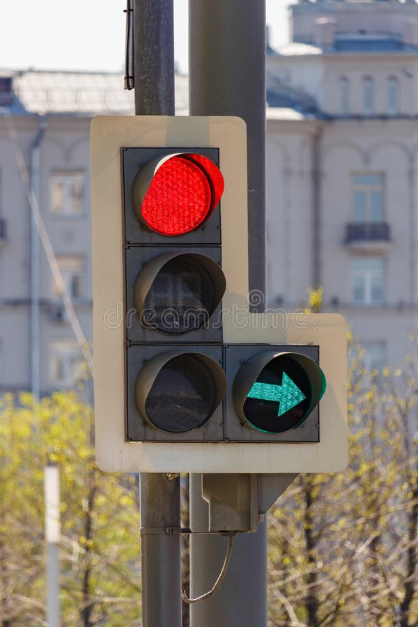 Traffic light with forbidding red signal and permissive green signal of right arrow section on city street in sunny day closeup royalty free stock photo