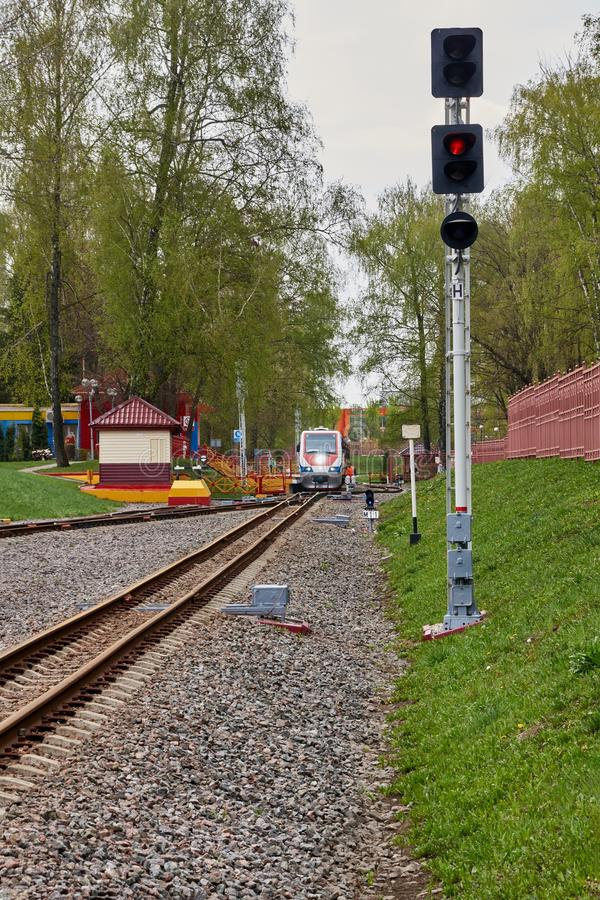 Traffic light narrow-gauge railway. Railway traffic lights in the background of the locomotive of the narrow-gauge children`s railway. Novomoskovsk, Tula, Russia stock photography