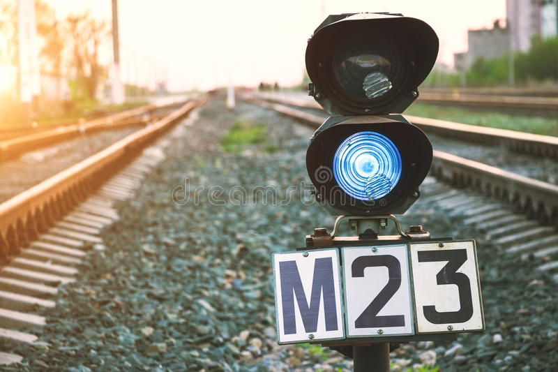 Traffic light shows blue signal on railway. Prohibiting signal. Railway station. Rail transportation. Traffic light shows blue signal on railway. Prohibiting stock photo