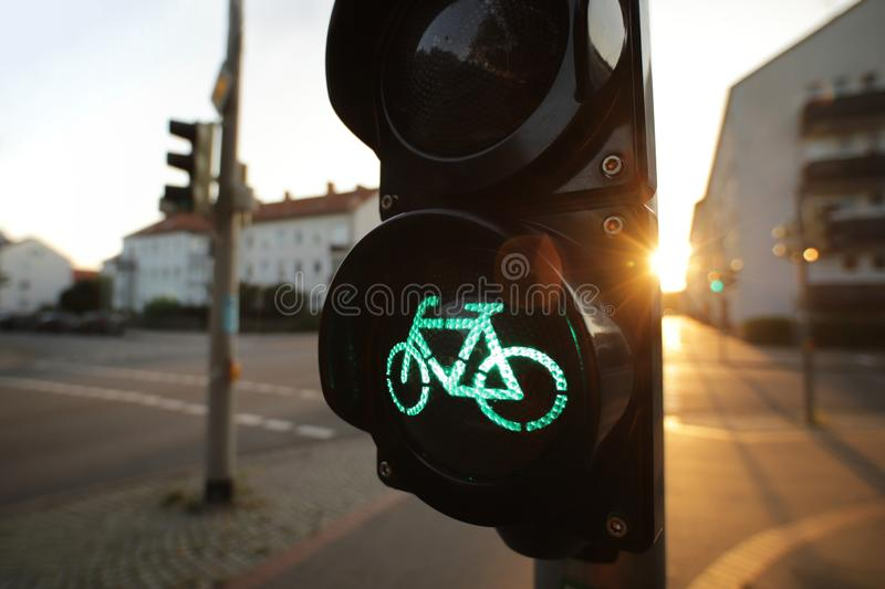 A traffic light shows green bicycle symbol at an european intersection in uplifting and inspiring morning light. Wide angle view on traffic light showing green stock photo