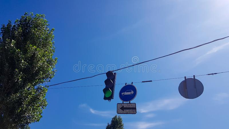 Traffic light and signs on the street close up with a burning green light.  royalty free stock photo