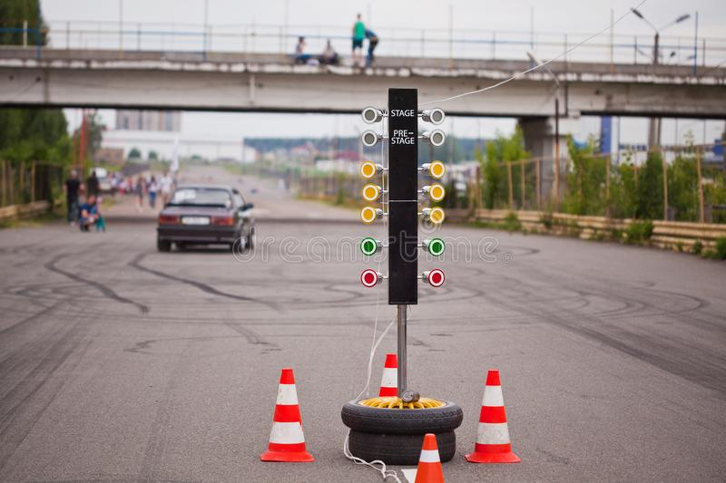 Traffic light at the start of a racing track with a car in the distance royalty free stock photography