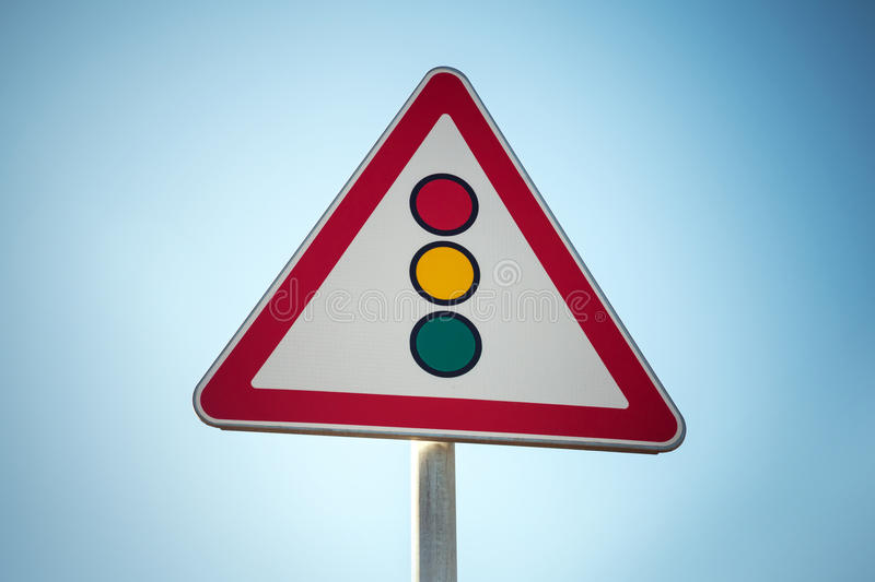 Traffic lights. Triangle road sign over blue sky background. Photo with vintage tonal correction filter royalty free stock image