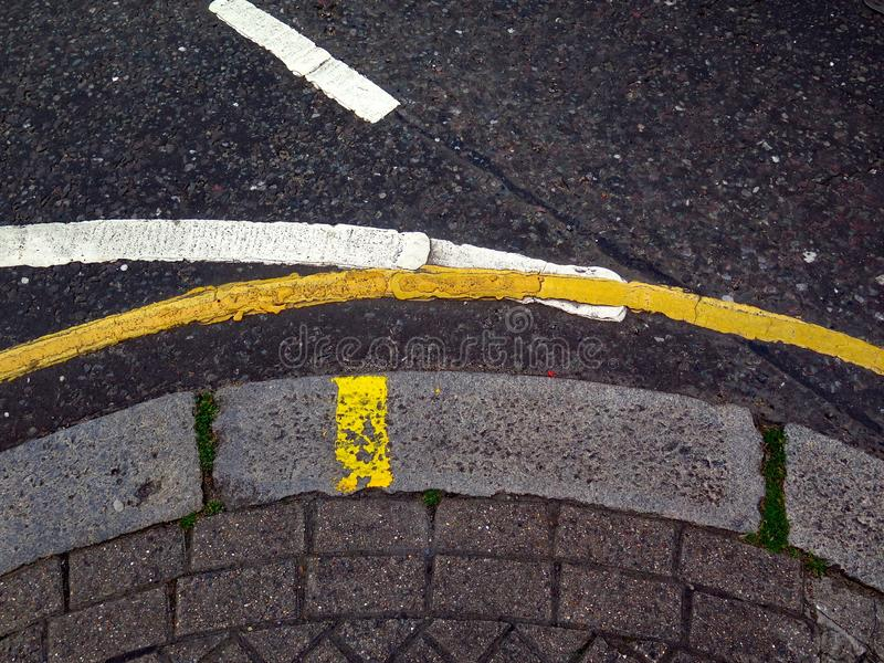 Traffic lines on bitumen and sidewalk in London. White and yellow traffic lines painted on the asphalt of a street in central London, UK. Stone border and paved royalty free stock photos