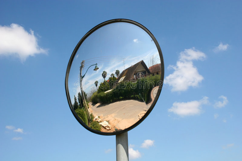 Traffic Mirror View. A rural house yard reflected in a traffic miror against a blue sky stock photos
