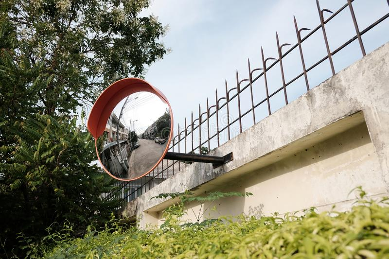 Traffic mirror on the wall at intersection or curve of road royalty free stock image