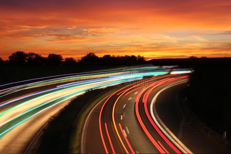 Traffic with motion cars with luminous speed lines and evening sky with beautiful sunset sky, natural landscape stock image