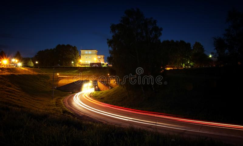 Traffic at night. Lights of the cars on the highway to the tunnel. stock photos