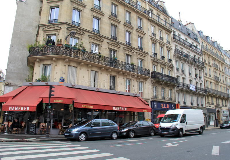 Traffic passing by busy corner, where Manfred Cafe Restaurant stands,Paris,France,2016. Beautiful craftsmanship in the old architecture where Manfred Café royalty free stock photos
