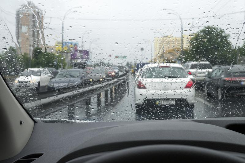 Traffic on the rainy day at the city street. View from the driver`s seat royalty free stock image