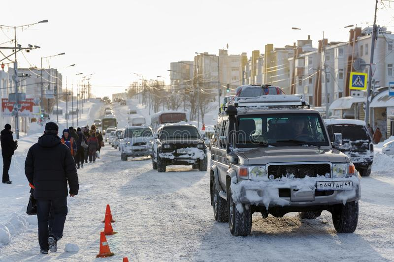 Traffic on road of capital of Kamchatka Region - people walk along the edge of road that is not completely cleared after snowstorm stock photo