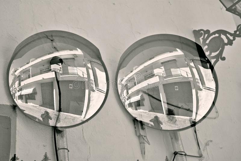 A traffic sign. A street mirror on a wall. This ia a photo with double exposition of a street mirror in Mijas Malaga royalty free stock photography