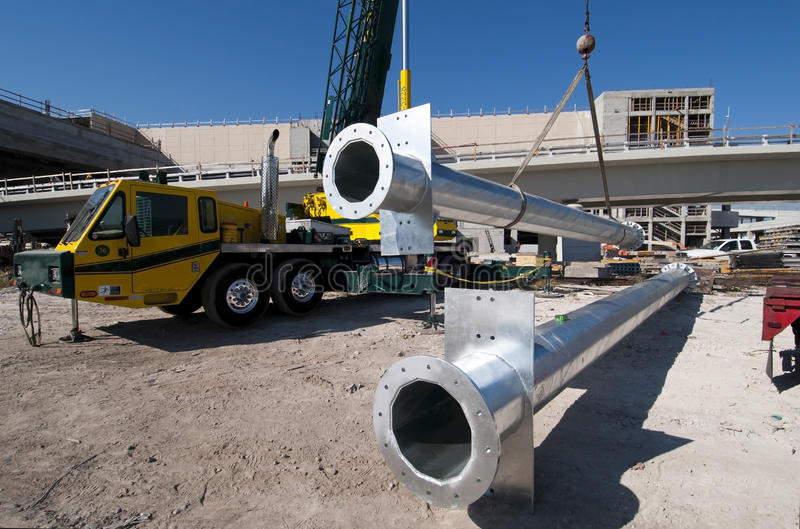 Traffic sign columns. Crane lifting a galvanized steel column for traffic signs stock images