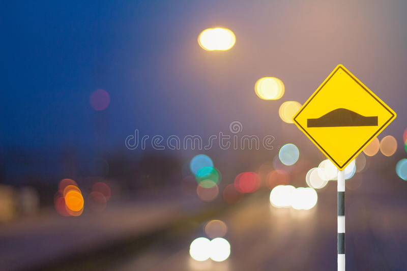Traffic sign and defocused lights bokeh as light car on road background in the industrial estate royalty free stock photo
