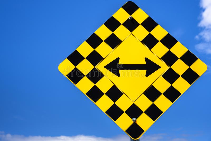Traffic Sign at an Intersection and Blue Sky. Double Aroow Traffic Sign with a Checked Pattern Blue Sky in Background. Concept of Choice and Options royalty free stock photo