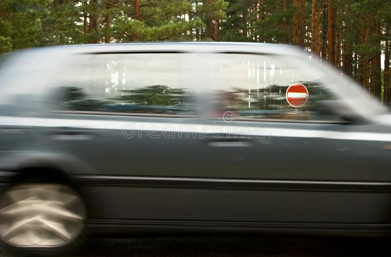 Passing car and traffic sign. Traffic sign `No entry` through a window of the passing car royalty free stock image