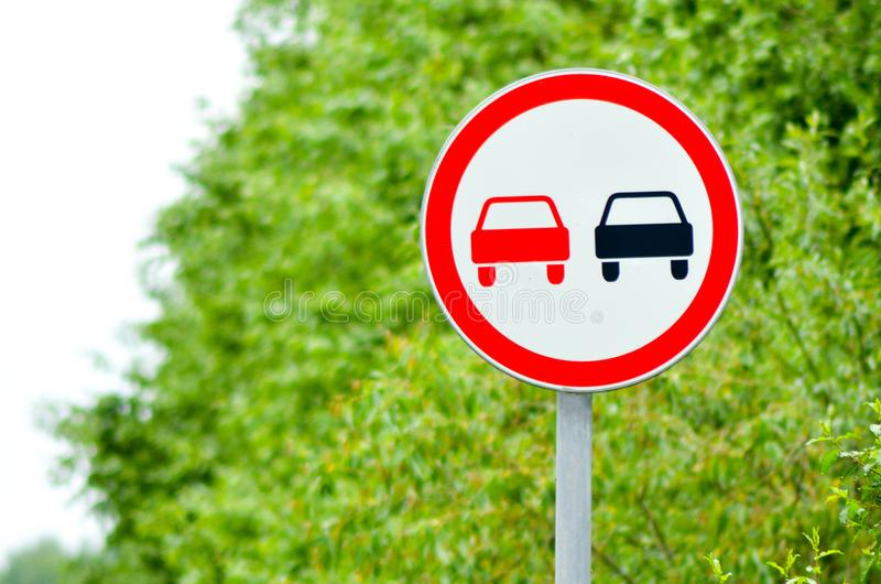 Traffic sign overtaking is forbidden in suburban highway. Traffic sign overtaking is forbidden in russian suburban highway against the background of the forest stock photo