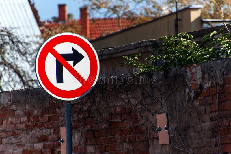 The traffic sign prohibits turning right at the old brick wall. royalty free stock photo