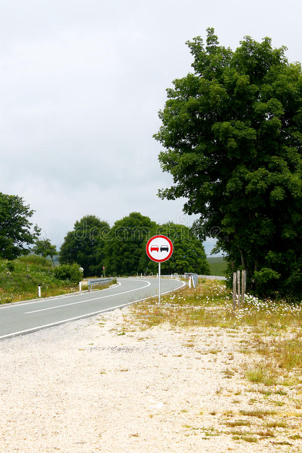 Download Traffic Sign On The Side Of A Winding Road Stock Image - Image of tree, cloudy: 91311263