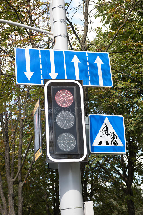 Traffic Sign on the Street. A traffic signal in front of the Osipovichi forest indicating directions and traffic signs for pedestrians. The clear, morning sky is stock images