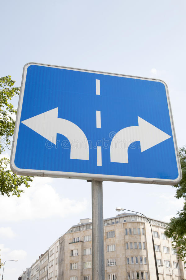 Traffic Sign in Urban Setting. Traffic Sign with Two Arrows Pointing in Different Directions stock photo