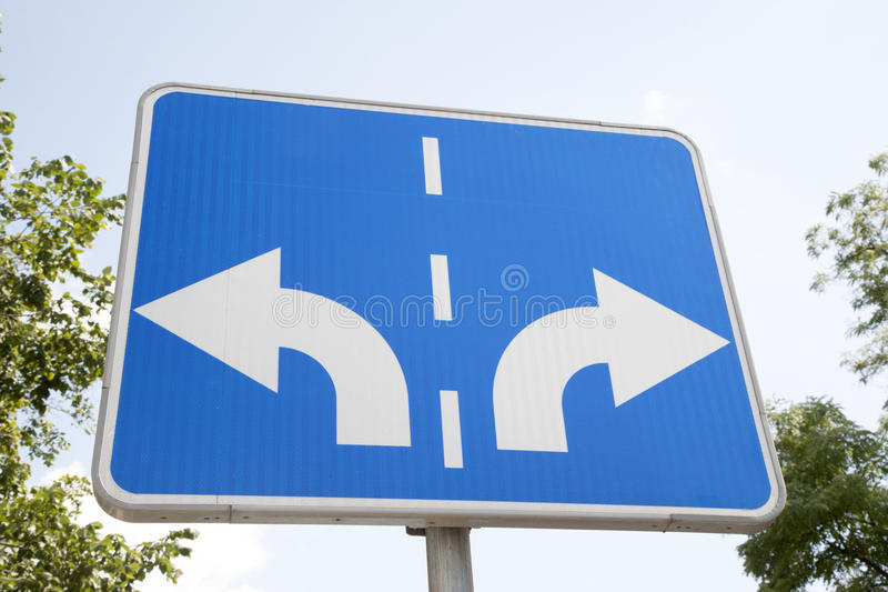 Traffic Sign in Urban Setting. Traffic Sign with Two Arrows Pointing in Different Directions stock photos