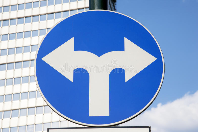 Traffic Sign in Urban Setting. Traffic Sign with Two Arrows Pointing in Different Directions royalty free stock images