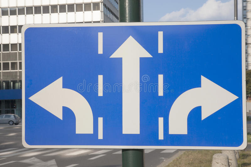 Traffic Sign in Urban Setting. Traffic Sign with Two Arrows Pointing in Different Directions stock images