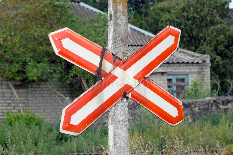Traffic sign a white cross with a red outline pinned to a pillar against the background of an old house. stock images