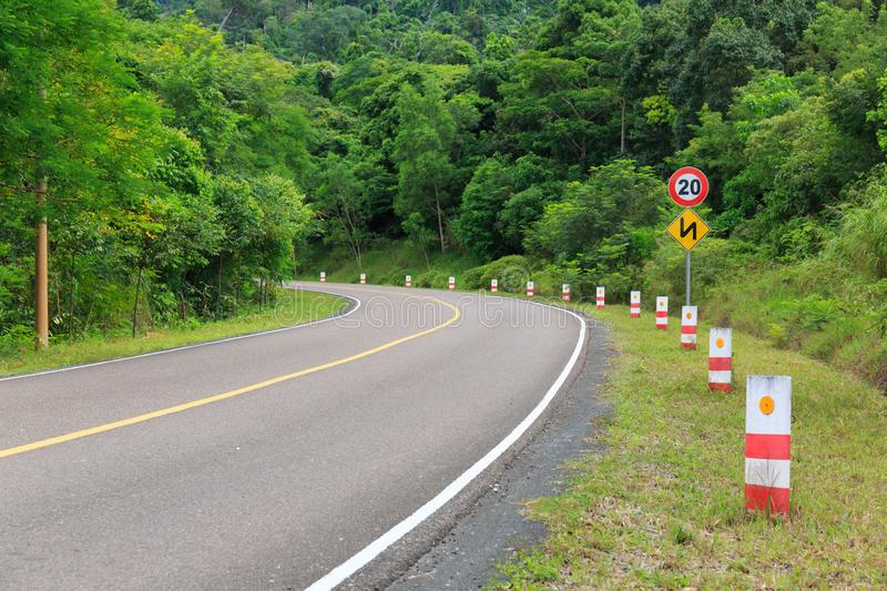 Traffic Signs and Bending Road to the Top of a Mountain with Green Trees stock images