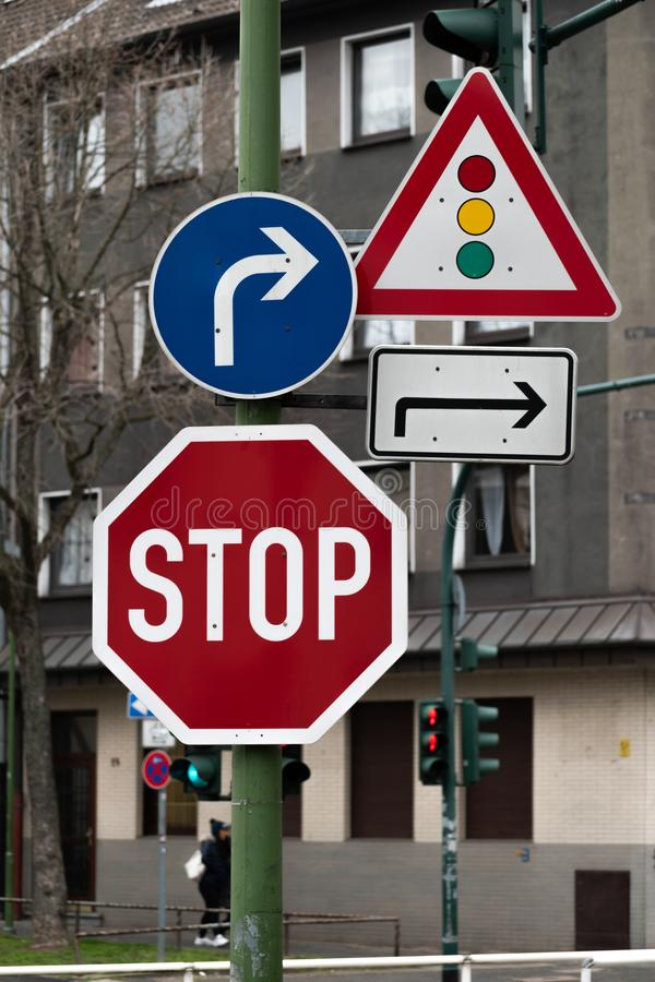 Traffic signs of caution and direction. Traffic signs for direction and stop, along with pedestrian lights in the background stock photos