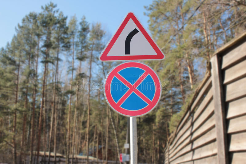Traffic signs give way and you can`t stop. In a forest and fences royalty free stock photos
