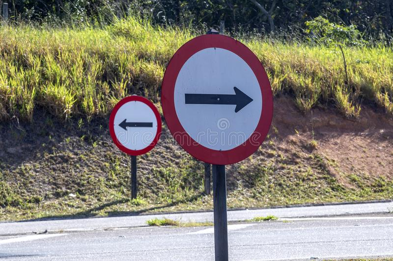 Traffic signs of mandatory direction. On opposite sides of the road royalty free stock image