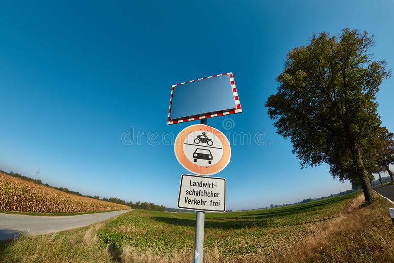 Traffic Signs and Mirror at Country Road with deep blue Sky.  royalty free stock photography