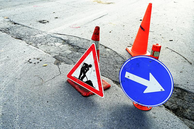 Traffic signs of road construction. In front of a road crack. Traffic sign arrow royalty free stock photography